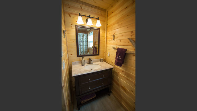 The full bathroom contains a bathtub, shower and vanity.