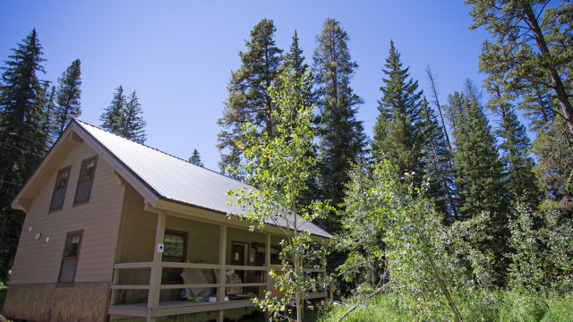 The Ursa cabin is nestled next to aspen and pine trees.