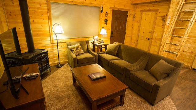 The living area has a loveseat and two chairs, perfect for game night!