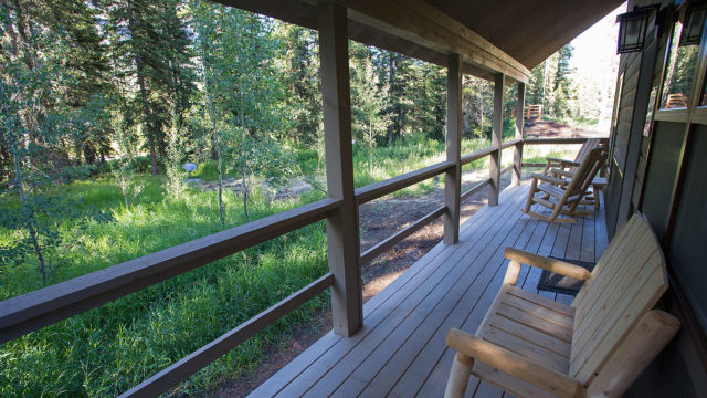 Relax on the porch, which faces the trees and Soda Butte Creek.